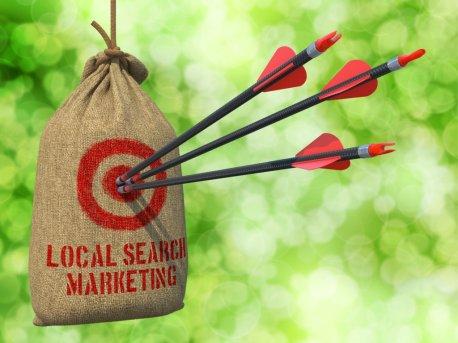 Local Search Marketing - Three Arrows Hit in Red Target on a Hanging Sack on Green Bokeh Background.