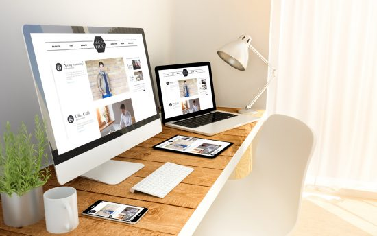 Desk with different electronics on it displaying a website design from a South Holland website design company